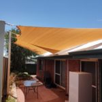 2 shade sails over paved area