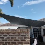 slate shade sail covering an outdoor paved area